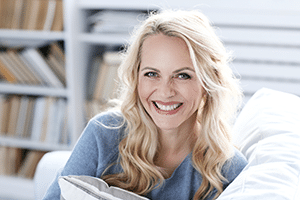 blonde woman sitting on couch smiling