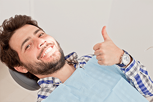 Hip young man gives the thumbs up to great dental care