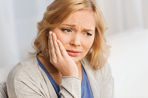 Woman holding side of mouth in pain
