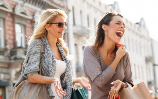 Two young woman with shopping bags in their hands walk down the street, laughing together