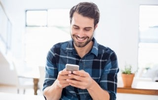 Hip young man grins and checks his phone