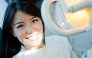Asian American woman shows off her bright smile sitting in a dental chair ready for her cleaning