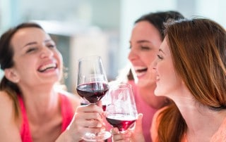 young women enjoy a glass of wine together