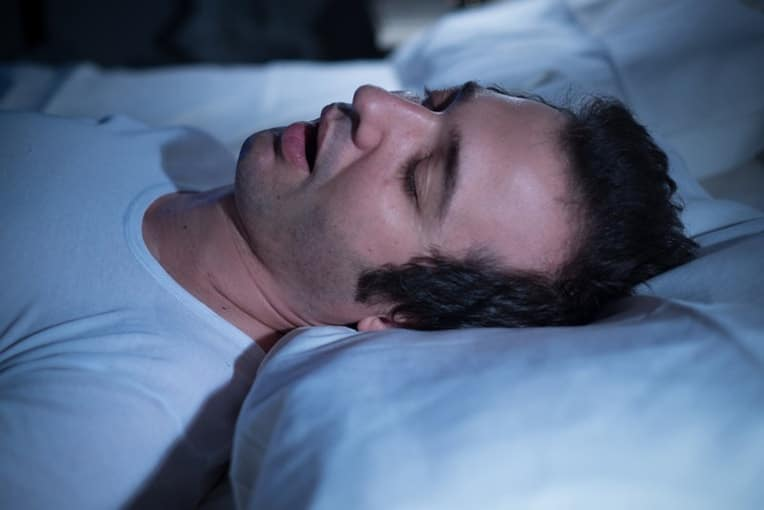 Man with short black hair sleeps in the dark with his mouth open, snoring. There are a number of at-home remedies to stop snoring, but not necessarily for Sleep apnea.