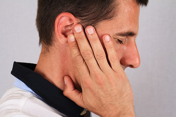 Male holding his hand next to his ear due to pain