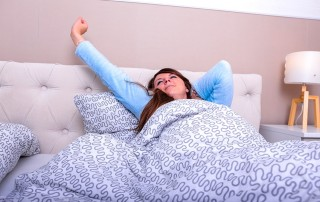woman stretching in bed after a restful nights sleep
