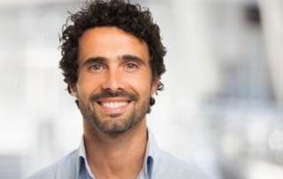 Man with short curly hair shows off his bright smile
