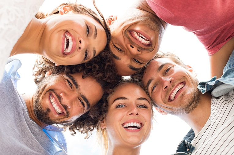 Happy group of friends putting their heads together smiling