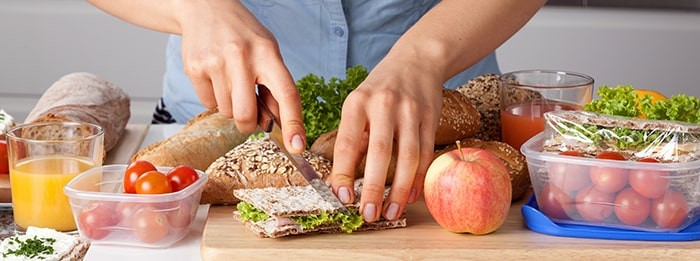 Female hands cutting a healthy sandwich on a countertop. Eating better may help your migraines