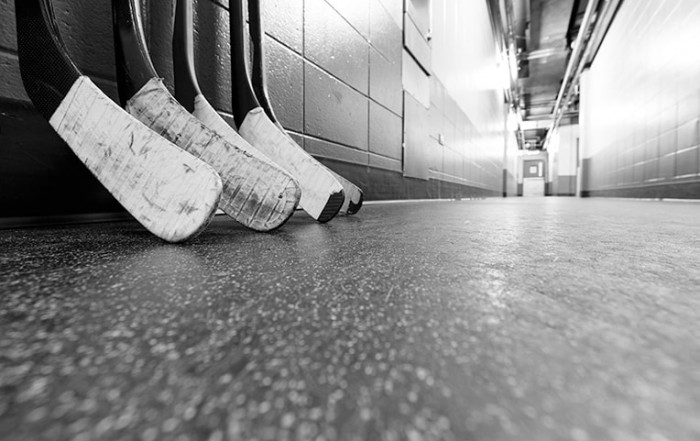 A set of hockey sticks rests up against a wall after a playoff game. While everyone loves a good hockey fight, have you ever thought about what happens when I player has their teeth knocked out?