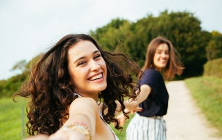 Two young women pulling a third while laughing and running without a worry in the world. While they could damage their mouth if they fall - they won't damage their mouth with teeth whitening by Los Gatos cosmetic dentist Dr. Nancy Nehawandian.