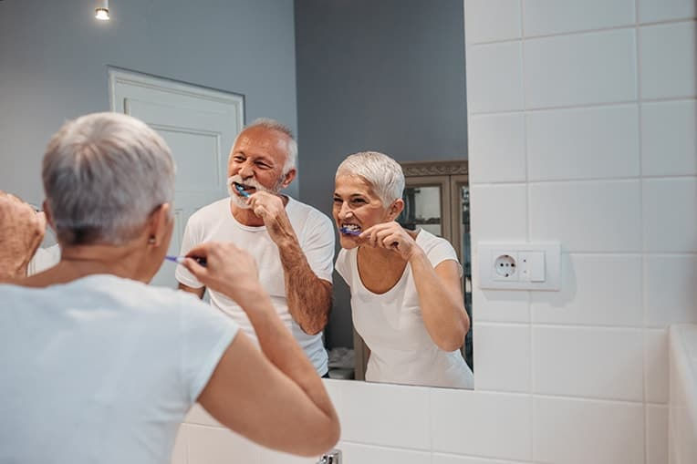 Happy older couple standing in front of bathroom mirror while brushing their teeth. A recent study shows that gingivits bacteria is linked to Alzheimer's disease, making it even more important to brush as we age.