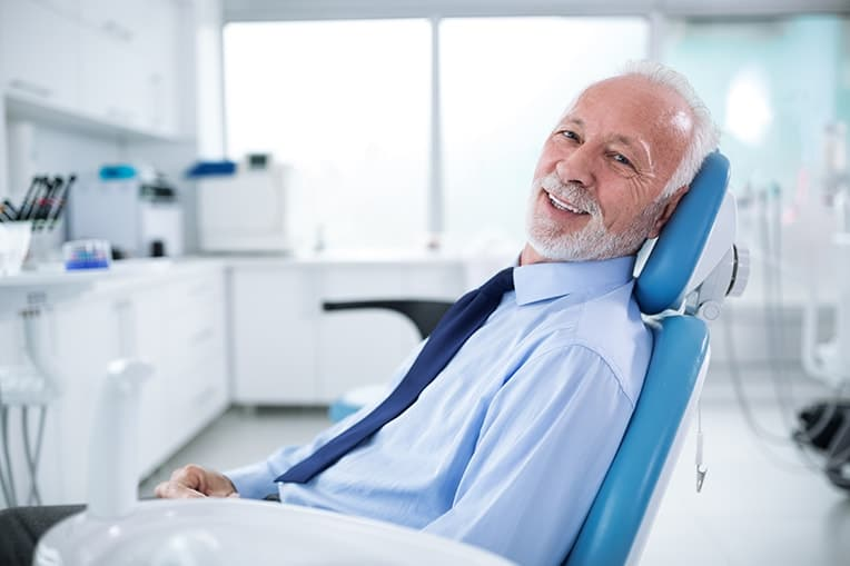 Older man sits in a dental care, awaiting his exam. Even with dentures you should schedule a routine exam to take care of your oral health.