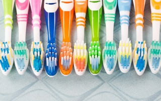 A group of toothbrushes sitting next to eachother. When thinking about what type of toothbrush you should use what is the best?