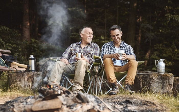 A Father and son enjoying a camping trip and conversation with each other