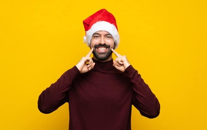 A jolly man with a Santa hat on smiles, showing his grin. How are you taking care of your oral health this holiday season?