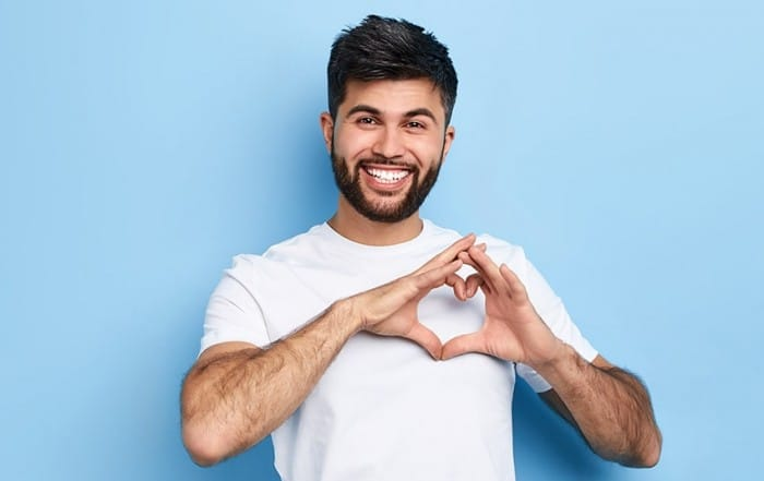 Young bearded man places his hands on his chest in the shape of a heart