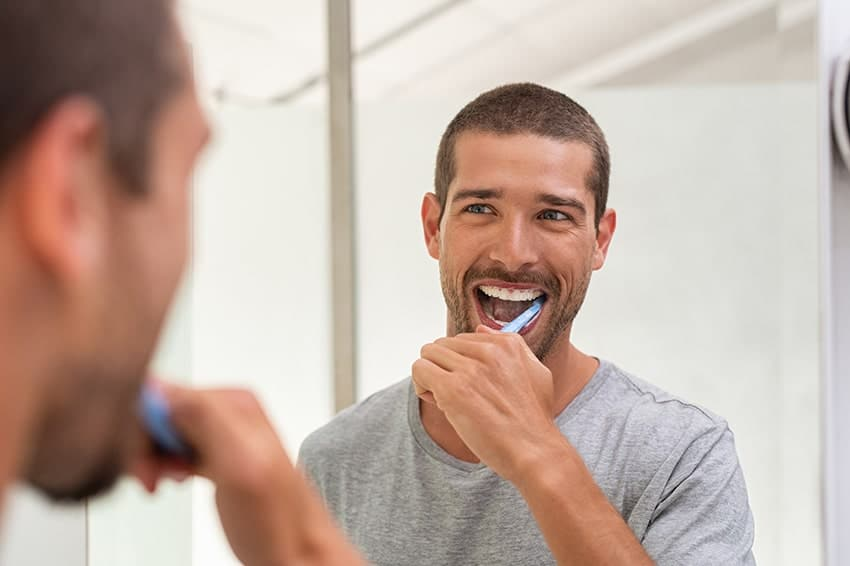 Attractive man stands in front of the mirror while brushing his teeth