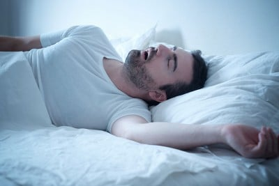 man laying on his back, snoring loudly at night