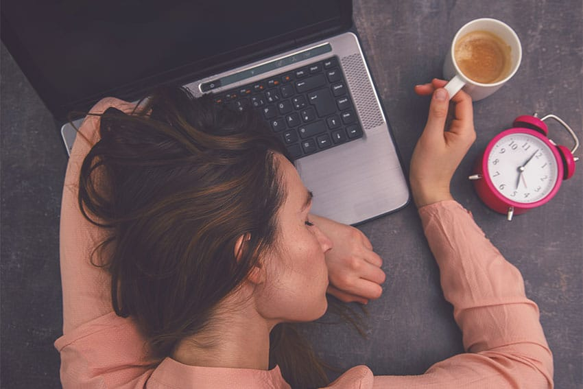 woman sleeping on top of her laptop, holding a coffee
