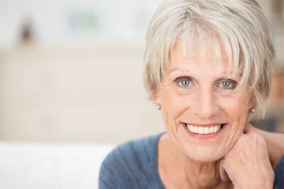 mature woman leans in, showing her happy, youthful smile