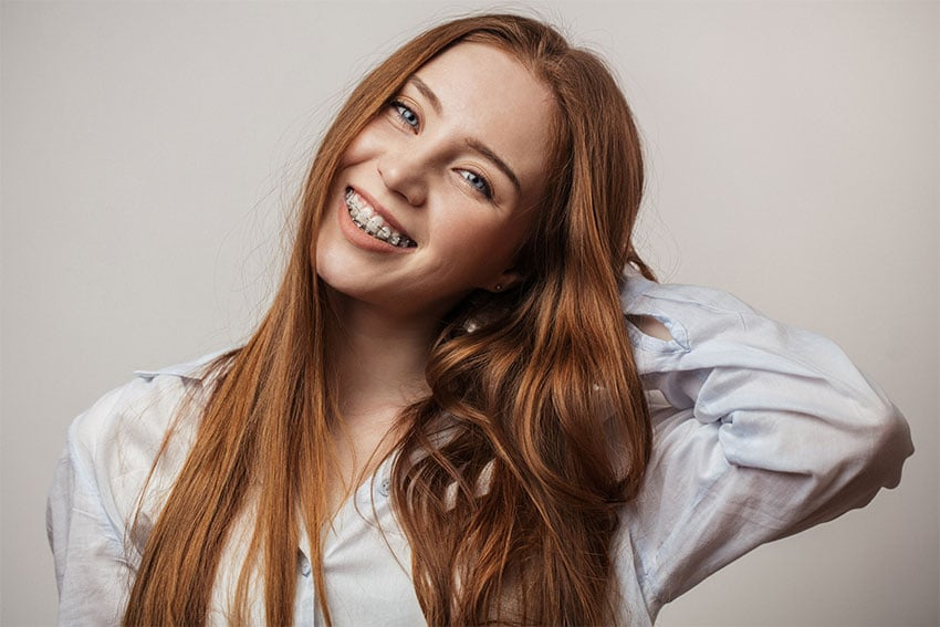 young red haired girl holds her hand behind her neck while tilting her head and smiling, showing off her braces