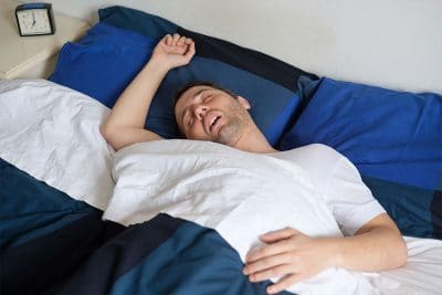 large man sleeping hard in bed, snoring, with his arm over his head