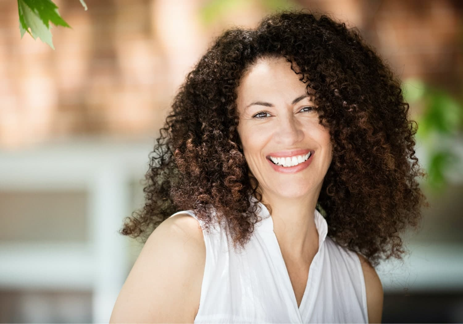 woman with curly hair shows off her healthy smile