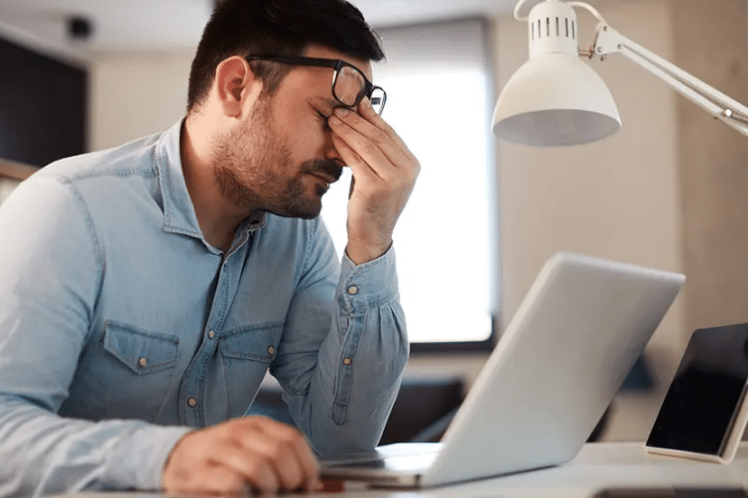 stress out man shows sits at his laptop, working