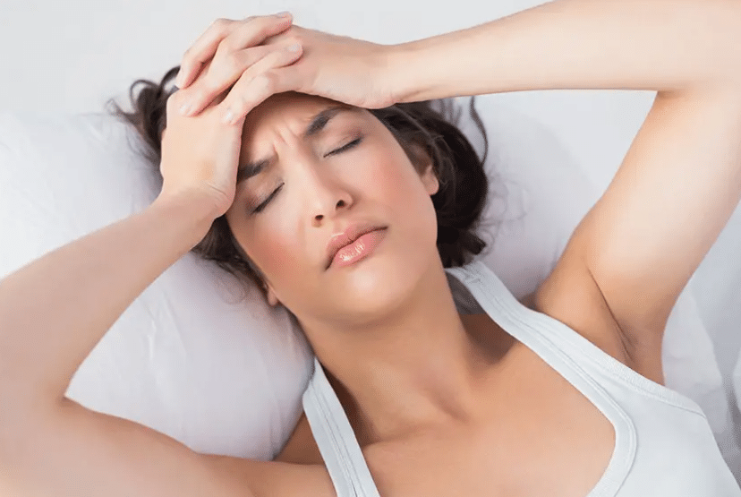 woman suffering from migraine while laying in bed