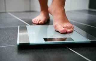 woman's bare foot stepping on a weight scale in the bathroom
