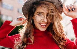 woman in large eye glasses and fancy hat shows off her smile